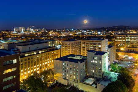 Full moon rising over Portland Oregon downtown cityscape during evening blue hour