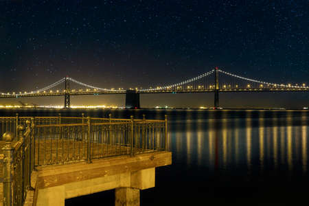 Oakland Bay Bridge brightly lit at night by the pier in San Francisco California
