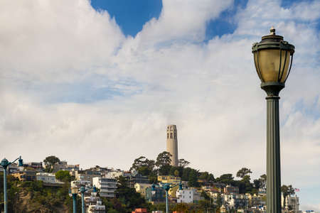 View of Telegraph Hill Neighborhood and Coit Tower from the pier by lamp post in San Francisco California