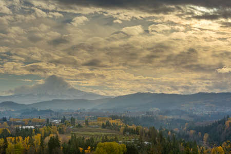 Rolling Clouds over Mount Hood and Sun Rays over Hood River Valley Oregon fruit orchard during fall season
