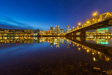 Portland Oregon city downtown skyline by Hawthorne Bridge during evening blue hour