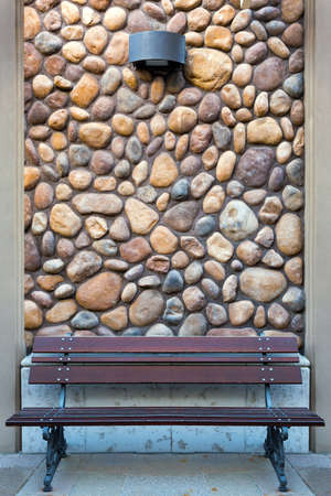Outdoor garden wood bench on pavement by river stone rock wall