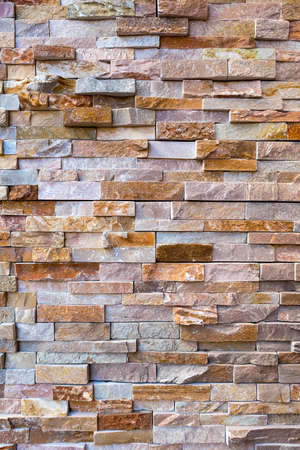 Stacked stone rock wall on building exterior background Stock Photo