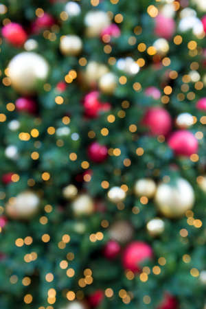 Christmas Holiday tree with round ball ornaments in gold red silver lighting blurred defocused bokeh background Stock Photo