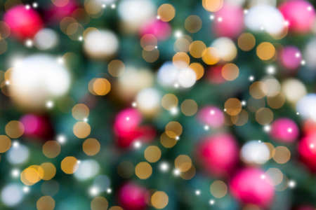 Christmas Holiday tree with round ball ornaments in gold red silver twinkle sparkles lighting blurred defocused bokeh background