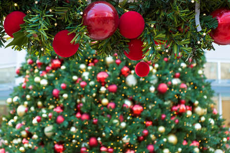 Christmas holiday tree garland decorated with red round ornaments and Christmas tree background Stock Photo