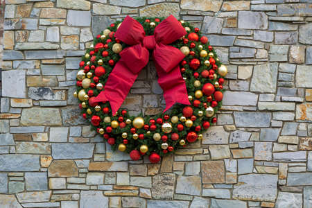 Christmas Holiday Wreath with red bow ribbons ornaments hanging on rock stone wall