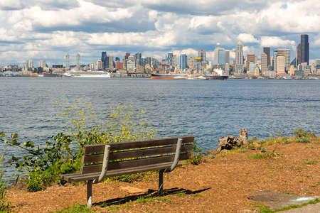 View of Seattle Washington city skyline along Elliott Bay by wooden bench in Alki Beach