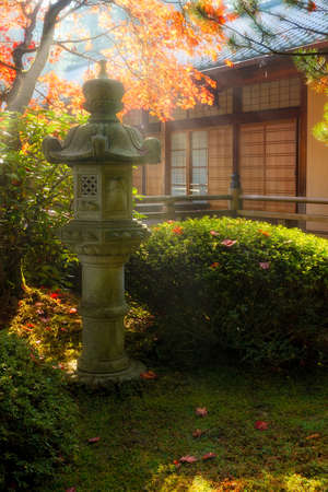 Sun beams over stone pagoda lantern by the pavilion at Japanese Garden during fall season