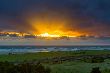 Sun rays beams in the sky over boardwalk in Long Beach Washington State during sunset