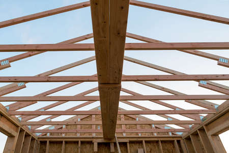 Roof support beams and wood studs framing in new home construction Stock Photo