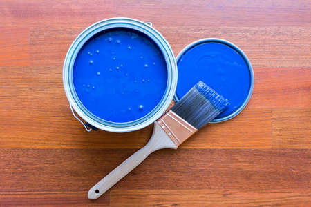 Top view of blue paint can and brush on cherry hardwood floor background