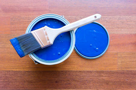 Top view of blue paint can and brush on top with cherry hardwood floor background