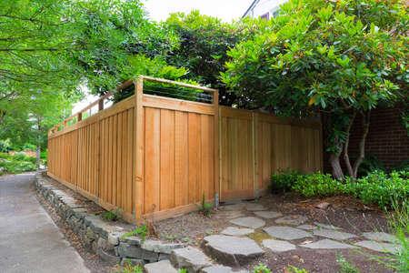 Nueva cerca de madera de cedro con puerta de entrada en el jardín del lado de la casa