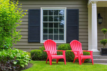 Red outdoor chairs on green grass lawn of house manicured front yard