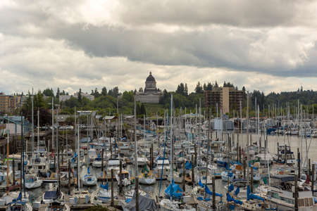 Marina with boats moored in Olympia Washington State by Capitol building on a cloudy day