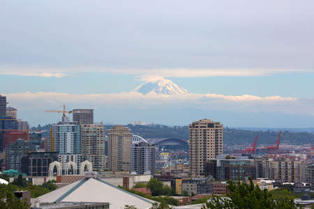 Seattle Washington downtown city skyline with Mount Rainier partially covered in clouds