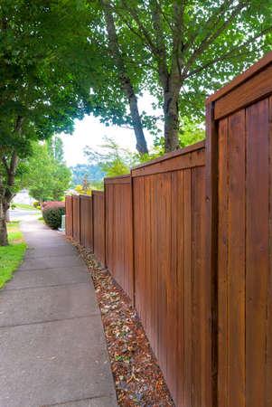 Wooden Fence along suburban neighborhood sidewalk Stock Photo