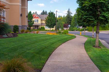 Huis voortuin en parkeerstrook vers gemaaid groen gras gazon in Noord-Amerikaanse buitenwijk Stockfoto