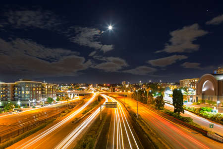 Moon Rise over freeway with long exposure light trails in Tacoma Washington at night