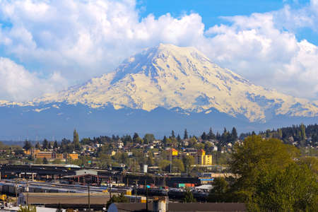Mount Rainier over Port of Tacoma Washington industrial area and I-5 Interstate freeway on a cloudy day Stock Photo