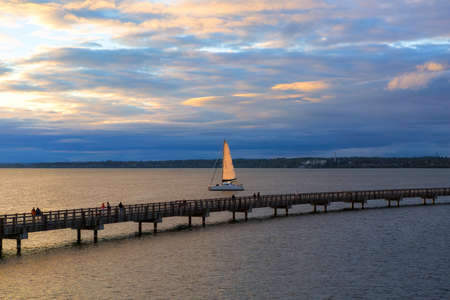 Sailing on Bellingham Bay by boardwalk at Boulevard Park in Bellingham Washington State during sunset Stock Photo