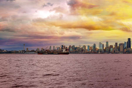 Seattle Washington city skyline along Elliot Bay in Puget Sound from Alki Beach during sunset Stock Photo
