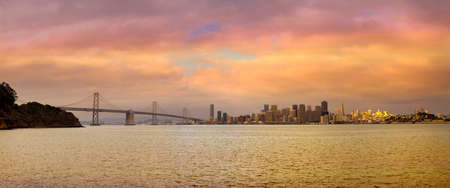 San Francisco CA city skyline and Oakland Bay Bridge during sunset panorama