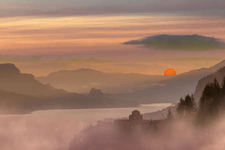 Foggy hazy red sun sunrise morning at Crown Point in Columbia River Gorge Oregon