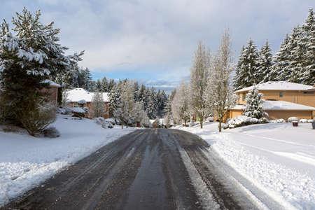 Suburban neighborhood street with de-icing salt plowed during one winter snow day in Happy Valley Oregon