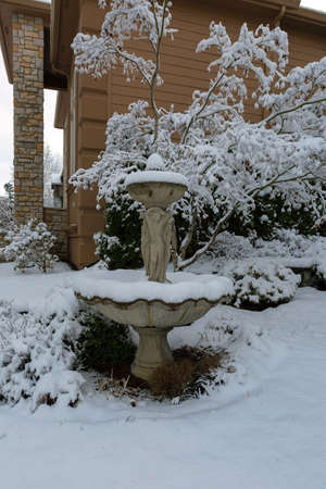 Snow covered water fountain in home garden front yard in suburban neighborhood during winter season