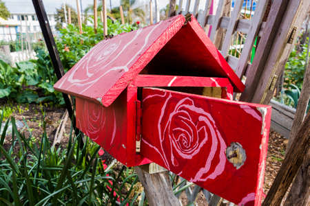 st kilda: A red wooden letterbox with a white painted floral patern on its roof and door. Found in a community garden in St Kilda, Melbourne.