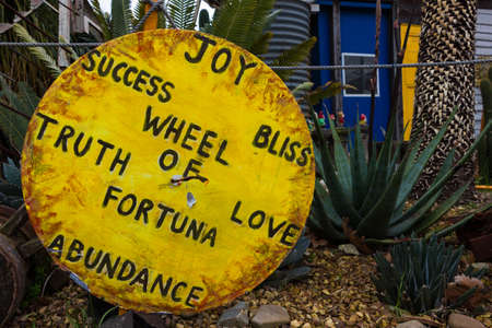 abundance: Large round yellow sign with loving messages painted on it with foliage in the background.