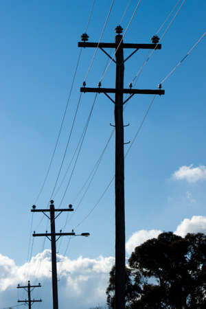 switchgear: Silhouette of Overhead Power Lines and Poles with cloudy skies.