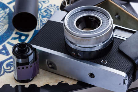 rangefinder: An old Rangefinder camera with film and canisters placed on a book.