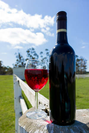 glass fence: A red wine bottle and glass resting on a white fence in the country.