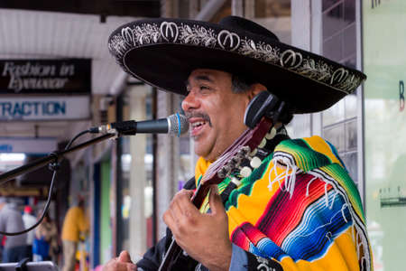busker: MELBOURNE  AUSTRALIA - SEPTEMBER 5 2015: Hampton Street Fathers Day Car Show - A Mexican Busker playing to a crown during the Fathers Day Car Show at Hampton, Melbourne.