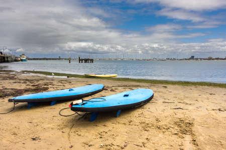 st kilda: Three surfboards resting on a quiet beach in St Kilda, Melbourne.