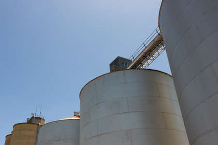 Large steel grain silos with cloudless blue skies. Stock Photo