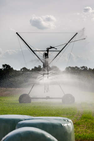 irrigating: Large agricultural irrigation system irrigating crop.