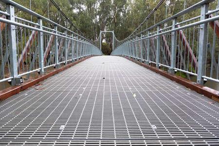 nestled: A large steel suspension foot bridge over a river nestled in the Australian bush.