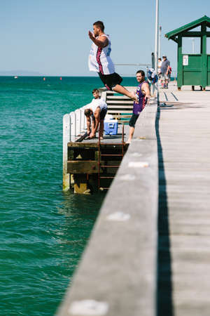 somersault: MELBOURNEAUSTRALIA - FEBRUARY 6: Youths jump off a jetty into the water, while others fish in Mordialloc, a coastal suburb of Melbourne, Australia in February.