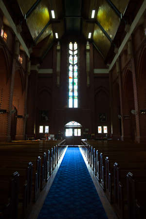 Interior of an old church with blue carpet running down the centre of the pews.