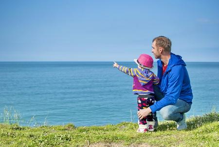 relaciones humanas: Demostraciones de la niña en el mar padre y le dice algo al lenguaje aparentemente sencillo sólo para ella. Foto de archivo