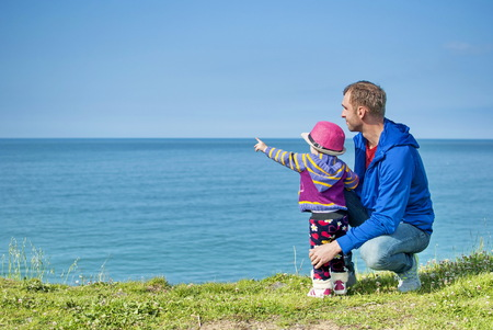 seemingly: Little girl shows on the sea father and says something to the seemingly plain language just for her.