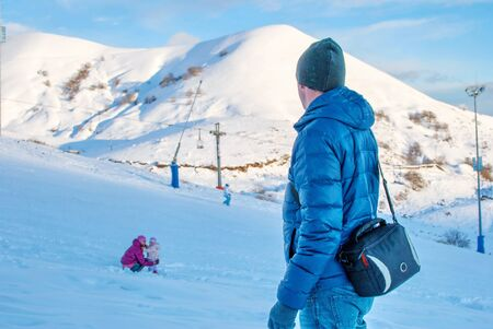 Father turned to hail daughter, next to which sits mother on a ski slope in the mountains