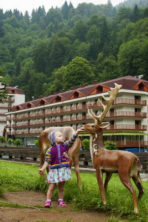 Little girl feeding deer statue on the background of the mountain forest.