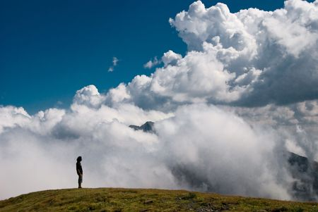 A man sitting in top of the mountain, and watching a clouds show, with the negoiu peak covered by clouds