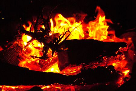A campfire in the night, next to a basecamp