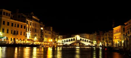 At the evening around the Grand Canal, The Rialto bridge under evening lights.